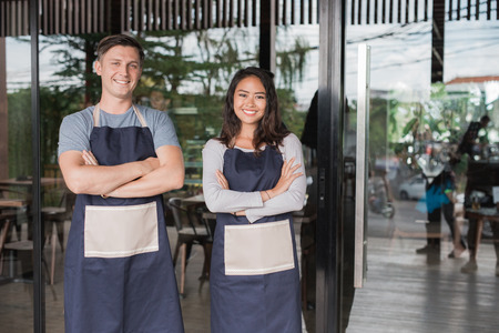 Successful male and female small business owner proudly standing in front of their cafe or coffee shop