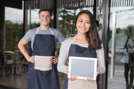 portrait of happy female waitress holding tablet pc and smiling to camera. her partner  at the background