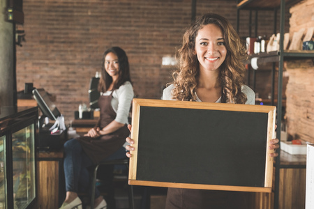 portrait of attractive female waitress standing and holding blank blackboard sign at a cafe
