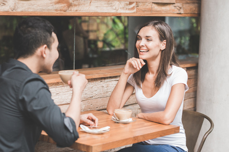 two happy mixed race couple having fun at the coffee shop