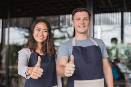 two waiter showing thumb up together while standing in front of their cafe