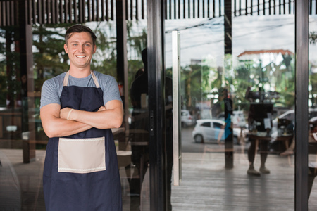 business owner standing in front of his shop Stock Photo