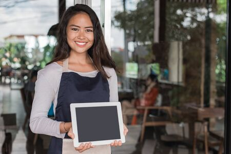 彼女の店の前でタブレットに立って若いカフェのオーナー