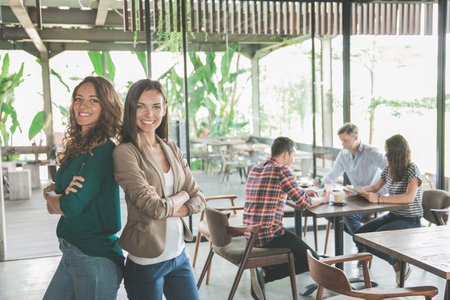 two mixed race woman standing together during their meeting in a cafe