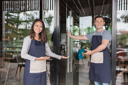 waiter welcoming customer to come to their newly open cafe