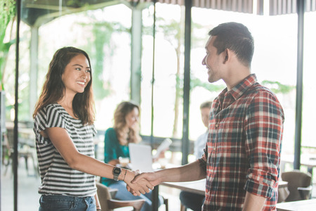 young business meeting in coffee shop. two partner shake hand Stock Photo