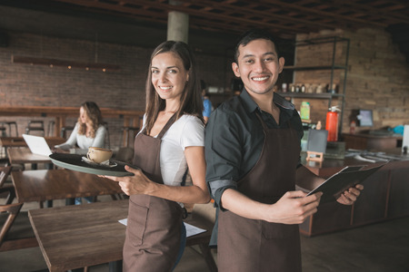 two male and female waitress serving coffee at the cafe