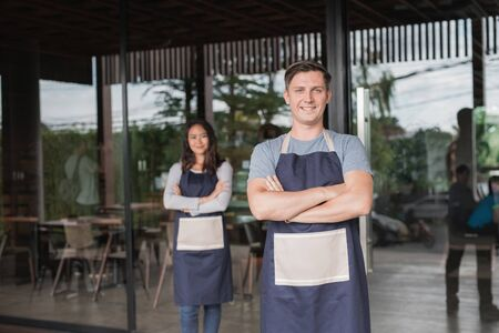 cafe owner standing with crossed arms and his partner at the background Stock Photo