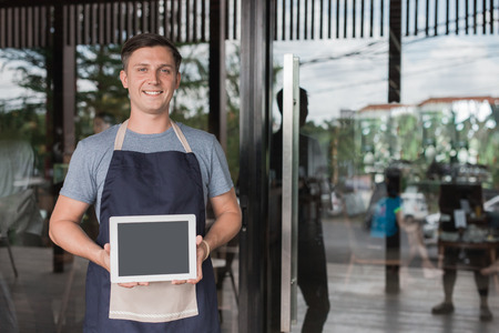 portrait of confident young asian male cafe owner standing with tablet pc