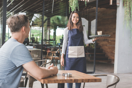 portrait of a female waitress serving coffee to a male customer