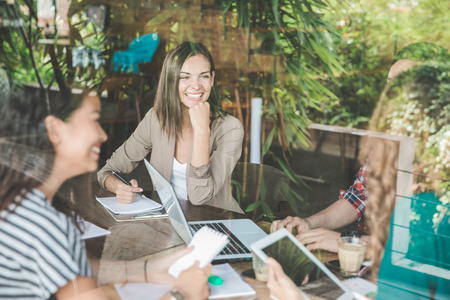 happy businesswoman smiling while meeting with her team at coffee shop
