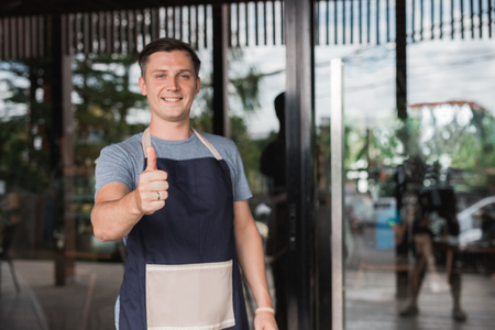 proud business owner showing thumb up to camera
