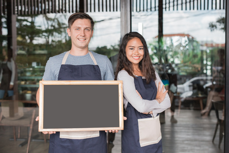 male and female cafe owner proudly standing in front of their cafe or coffee shop holding blackboard Stock Photo