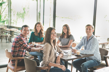 diverse business team meeting in a coffee shop looking at camera
