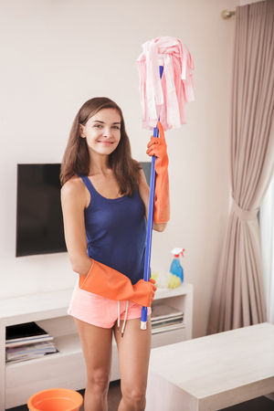 portrait of beautiful housewife holding a mop at livingroom Imagens