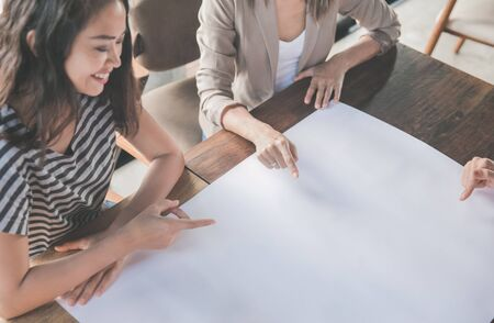 portrait of businesswoman pointing at their plan on paper during team meeting