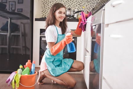 portrait of housewife smiling while cleaning a kitchenware using cleaning spray and duster