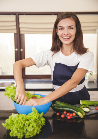 portrait of beautiful happy housewife preparing vegetables for cooking at kitchen Фото со стока - 92566294