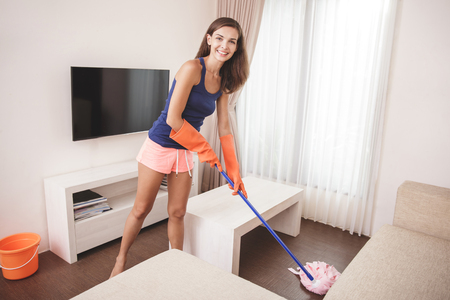 Portrait of beautiful housewife cleaning the floor at living room using mop 版權商用圖片