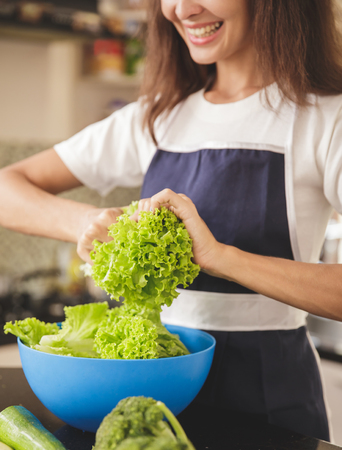 Close up portrait of housewife preparing lettuce for making salad