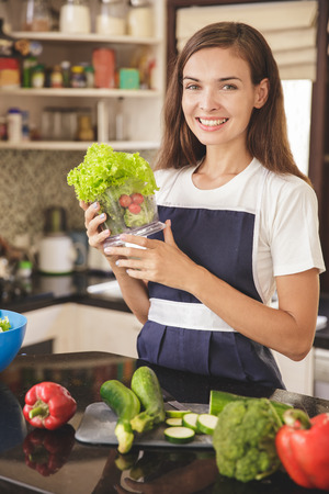 portrait of happy housewife preparing vegetables for making vegetables juice at kitchen