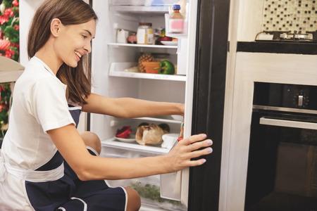 Ritratto di bella casalinga che cerca ingredienti di ingredienti alimentari in frigorifero Archivio Fotografico - 87871127