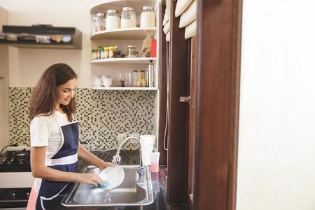 コピー スペースとお皿を洗う幸せな主婦の肖像画