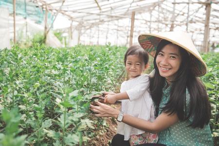 portret van moeder en haar dochter die samen in de boerderij bewerken Stockfoto