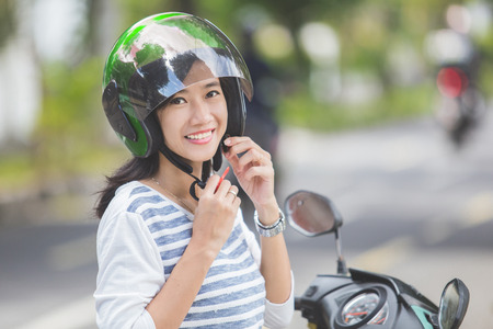 gelukkige vrouw bevestigingssystemen haar motorhelm in de stad straat Stockfoto