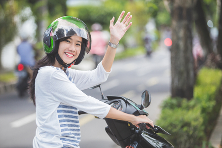 happy asian woman waving hand while riding on motorbike in city street