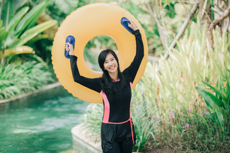 portrait of happy excited young woman with tube in a water park resort Stock Photo