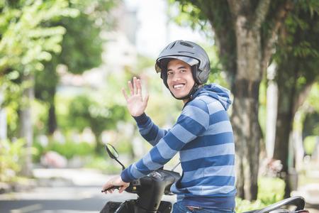 gelukkig Aziatische man zwaaiende hand tijdens het rijden op motor in stadsstraat Stockfoto