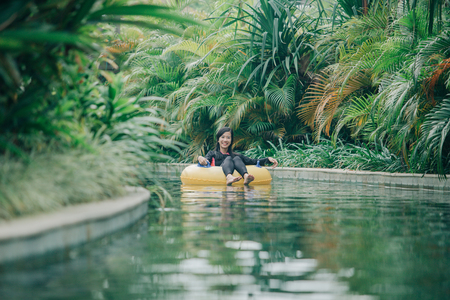 portrait of attractive asian woman relaxing at lazy river pool resort in summer day