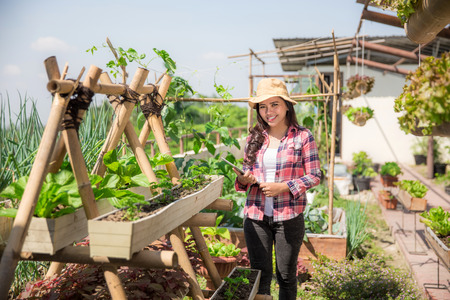 happy young asian woman in rooftop garden. small urban farming