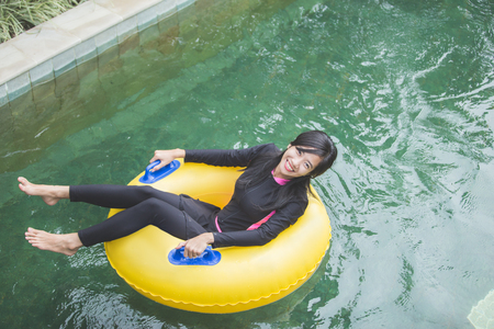 portrait of excited young woman enjoy tubing at lazy river pool