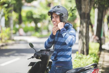Uomo felice che fissa il suo casco da motociclista nella strada della città Archivio Fotografico - 92566324