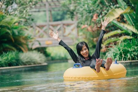 흥분된 젊은 여성의 초상화는 게으른 강물 수영장에서 튜빙을 즐기고 스톡 콘텐츠