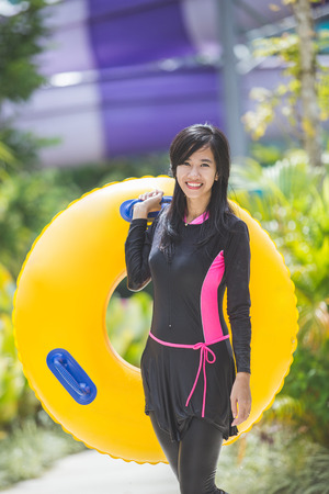 portrait of excited young woman with inflatable tube in a pool