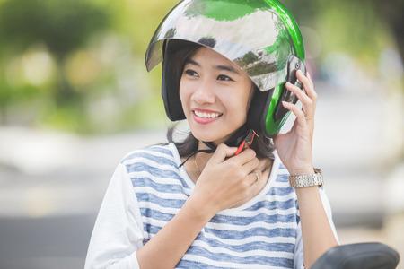 Donna felice di fissaggio suo casco da moto nella via della città Archivio Fotografico - 87974270