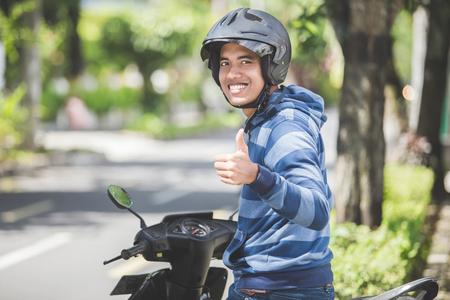 Retrato de hombre asiático feliz montando en bicicleta en la calle de la ciudad y mostrando pulgar Foto de archivo - 87974278
