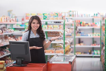 portret van jonge aantrekkelijke vrouw bij kassa in een winkel gastvrije klant Stockfoto
