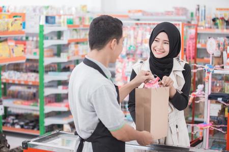 mujer musulmana feliz comprar el producto en la tienda de comestibles o supermercado