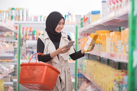 Felice giovane donna asiatica shopping al supermercato con la lista di controllo sul suo telefono cellulare Archivio Fotografico - 89451702