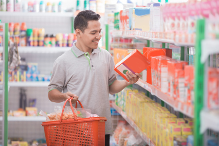 handsome young man looking at a product before put it into the basket in supermarket
