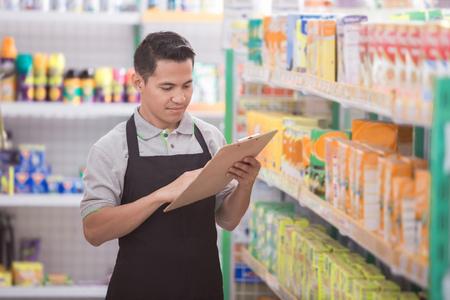 Commerçant masculin vérifiant la qualité du produit au supermarché Banque d'images - 92565189