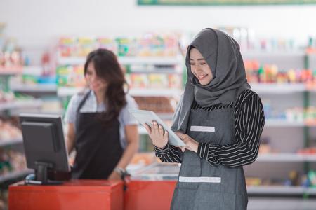 店内にタブレット pc を持つ若いムスリムの魅力的な女性の肖像 写真素材