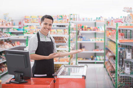 gelukkige jonge mannelijke winkelier gastvrije klant