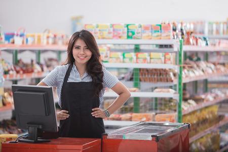 Portrait de souriant personnel féminin asiatique debout au comptoir de trésorerie dans un supermarché
