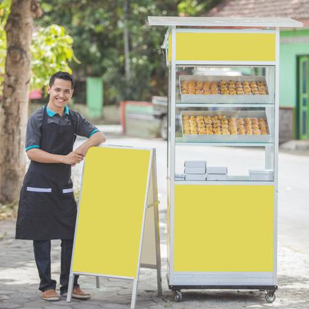 道の脇に彼のフードキオスクで立っているアジア人のビジネスオーナー。ストリートフードコンセプト