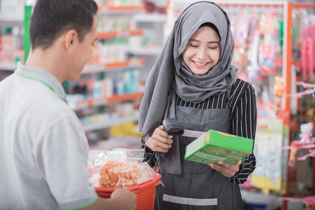 female muslim shopkeeper scanning product barcode in supermarket